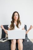 Young woman sitting on a couch with laptop and tablet to relax Royalty Free Stock Image