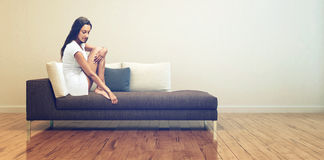 Young Woman Sitting on Couch at the Living Room Royalty Free Stock Photo