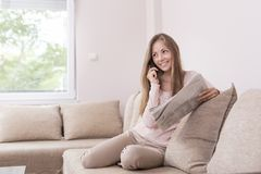 Phone conversation. Young woman sitting on the couch in a living room, reading a newspapers and having a phone conversation royalty free stock photo