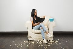 Reading and eating popcorn royalty free stock photo