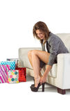 Young woman sitting on couch taking off her shoes Stock Photos