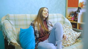 Young woman is sitting on the couch and watching TV. The woman switches the television channels. stock video