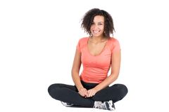 Young woman sitting cross-legged. Cut out image of a young woman wearing sports wear who is sitting cross-legged Royalty Free Stock Images