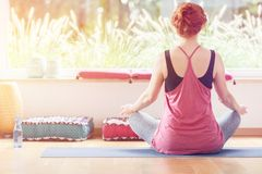 Young woman sitting cross-legged. On a sports mat during yoga classes at a peaceful gym Royalty Free Stock Images