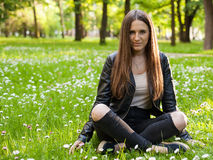 A young woman is sitting with crossed legs Royalty Free Stock Photography