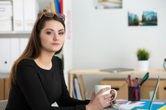 Young woman sitting with cup of tea at her office Stock Image