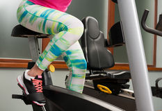 Young woman sitting and cycling on stationary bike Royalty Free Stock Images