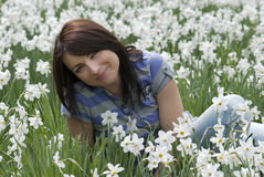 Young woman sitting among daffodils Stock Images