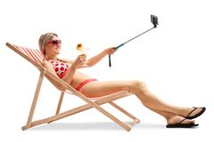 Young woman sitting in a deck chair and taking a selfie Stock Photos