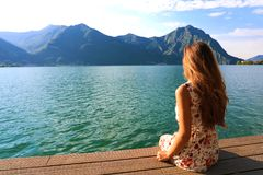 Young woman sitting on a deck by the water, looking into the distance. Carefree bright future concept. Back view beautiful woman stock images