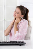 Young woman sitting at desk having pains in the neck or swollen. Young woman sitting in the office having ache in the neck or swollen lymph nodes stock image