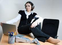 Young woman sitting on the desk with headphones Stock Images