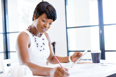 Young woman sitting at a desk in an office and working on blueprint Royalty Free Stock Photography