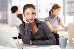 Young woman sitting at desk others working behind Royalty Free Stock Photos