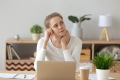 Young woman sitting at the desk and thinking royalty free stock photos