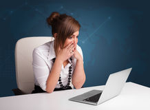 Young woman sitting at desk and typing on laptop Stock Photo