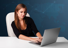 Young woman sitting at desk and typing on laptop Royalty Free Stock Images
