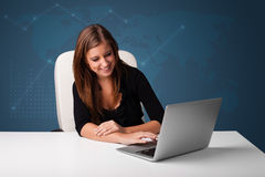 Young woman sitting at desk and typing on laptop Stock Photography