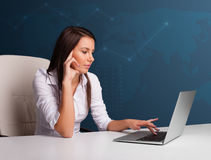 Young woman sitting at desk and typing on laptop Royalty Free Stock Photos