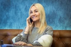 Portrait of young woman talking on phone and sitting in cafe royalty free stock photography