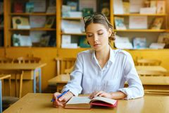 A young woman sitting at a Desk in a white shirt, a book on the table, a beautiful student stock photography