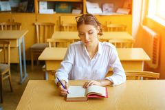 A young woman sitting at a Desk in a white shirt, a book on the table, a beautiful student stock images