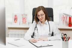 Young woman sitting at desk, working on computer, filling out medical documents in light office in hospital. Female stock image