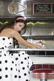 Young Woman Sitting At Diner Counter Royalty Free Stock Photography