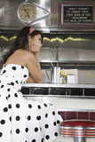 Young Woman Sitting At Diner Counter Stock Photography
