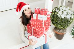 Young woman sitting on doorstep outside of rustic wooden house holding gifts stock photos