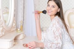 Young woman sitting at dressing table Stock Photo