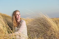 Young woman sitting in the dunes with long grass Royalty Free Stock Image