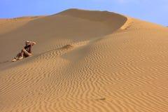 Young woman sitting on dunes, Thar desert, Jaisalmer, India Stock Image