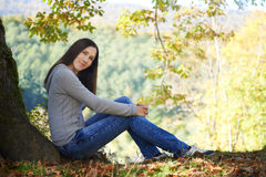 Young woman sitting on the edge of the cliff stock photos
