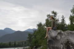 Young woman sitting on the edge of the cliff above the mountain river Royalty Free Stock Photo