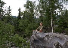 Young woman sitting on the edge of the cliff above the mountain river Stock Image