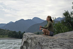 Young woman sitting on the edge of the cliff above the mountain river Royalty Free Stock Photos