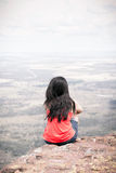 Young woman sitting at edge of cliff Royalty Free Stock Photos