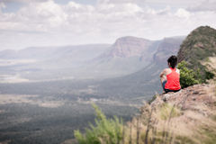Young woman sitting at edge of cliff Stock Image