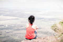 Young woman sitting at edge of cliff Stock Photo