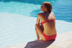 Young woman sitting on the edge of pool Royalty Free Stock Image
