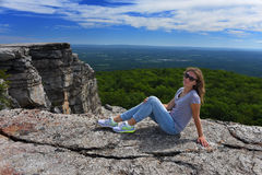 Young woman sitting at the edge of roc at Minnewaska State Park. Reserve Upstate NY during summer time Royalty Free Stock Images