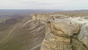 Young woman is sitting on the edge of tall wall of rock. Aerial View. Drone is flying fast backward. Over model at low angle. Establishing revealing shot stock footage