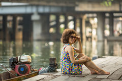 Young  woman is sitting on embankment of a city`s river. Stock Photography