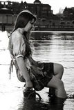 Young woman sitting on embankment and holding legs in water Royalty Free Stock Photos