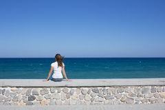 Young woman sitting on embankment Royalty Free Stock Image