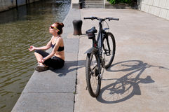 Young woman sitting on the embankment of the river next to the b Royalty Free Stock Images