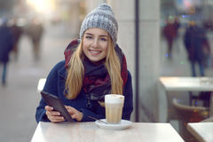 Young woman sitting enjoying a drink outdoors Stock Photography