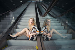 Young woman sitting on escalator Stock Photography