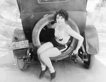 Young woman sitting in the extra wheel of a car Stock Photography